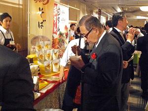 セブン&アイ・ホールディングスの伊藤雅俊名誉会長も交流・祝賀パーティー会場を訪れ、業務用加工食品ヒット賞受賞商品の一品一品を試食