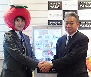 専用小型冷蔵庫を前に握手する川岸亮造KOM社長(左)と兵藤透キユーピー常務