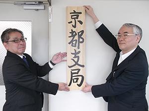 「京都支局」の看板を掛ける村上堅治局長(右)と藤田栄二支局長