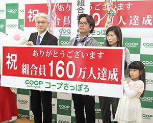 コープさっぽろ中島則裕専務理事(左)と160万人目となった三石さん家族