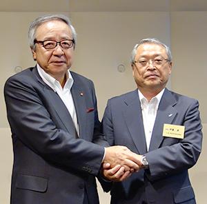 握手する伊藤雅俊前会長(左)と伊藤滋新会長