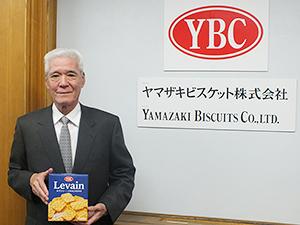 新社名ロゴ・新ブランドロゴを前に自信作のクラッカー「ルヴァン」を手にする飯島茂彰社長