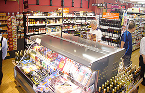 壁面にワインを展開し、平台でチーズやハムを関連販売