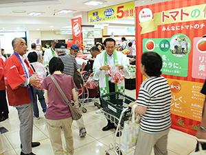 トマトを配布する大滝恭伸東京支社長(左端)と上田真社長(右から2人目)
