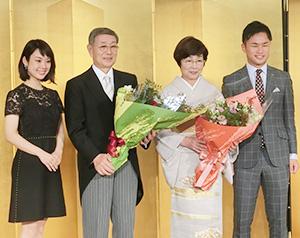 2人の孫による花束贈呈を受けた佐藤功会長(左から2人目)と俊子夫人(同3人目)