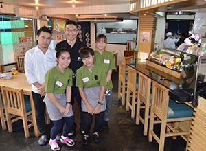 「従業員には伸び伸びと笑顔で接客してほしい」と話す橋本修一さん(後列中央)=タイ・バンコクで小堀晋一が16年12月18日写す