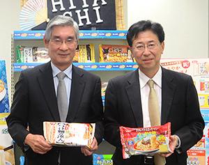春夏新商品を手にする吉本裕社長(左)と伊地知稔彦取締役マーケティング部長