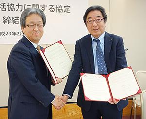 調印式後に握手する香川明夫学長(左)と村上健社長