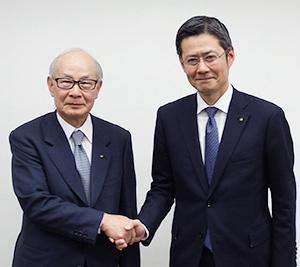 握手する國分勘兵衛会長兼社長(左)と國分晃副社長