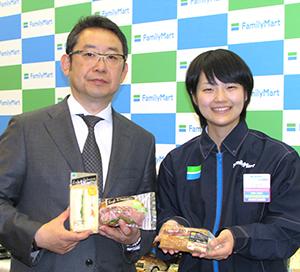 春の新商品を手にする佐藤英成商品本部長(左)