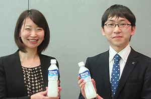 「カルピスウォーター」を手にする谷聡子副課長(左)と伊藤悠太副主任