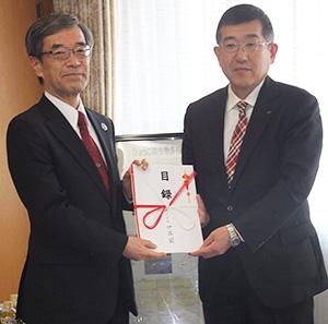 金澤和夫副知事(左)に目録を手渡す岡野浩也関西地域営業本部長
