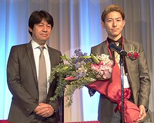 年間最優秀賞を受賞し主催者Eストアーの石村賢一社長(左)から花束を受け取ったジプソフィラの八木英士社長(18日、東京・新宿のホテルのパーティー会場で)