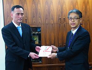 贈呈式で目録を手渡す村瀬忠久理事長(左)