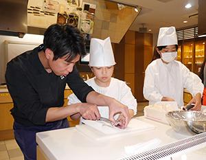 講師の高橋善郎氏(左)自ら、魚おろしを手ほどきした