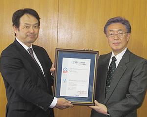 認証書を手にする平松賢介社長(左)とJQA中野昭彦ISO中部支部長