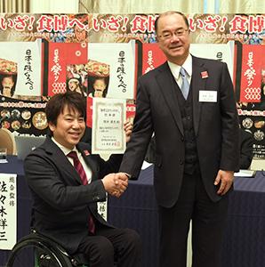 食博CSRアンバサダーに就任した根木慎志氏(左)と本荘武宏食博覧会実行委員会会長
