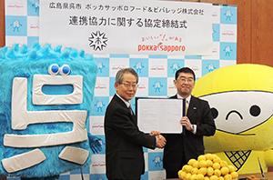 握手を交わす小村和年市長(左)と岩田義浩社長