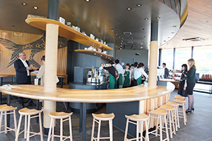 六甲山の木材を使用した流線型のカウンター、人魚のイラストパネルやうろこ状の壁が印象的な店内