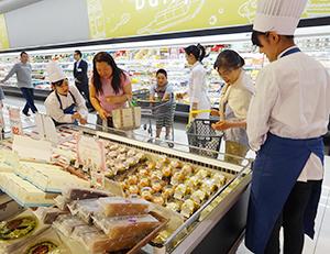 来店客に開発商品をアピールする学生