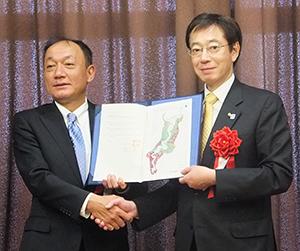 協定書を手にする布施孝之社長(左)と久元喜造市長