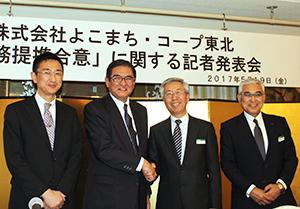 合意で握手する宮本弘理事長(中央右)と横町俊明社長(同左)
