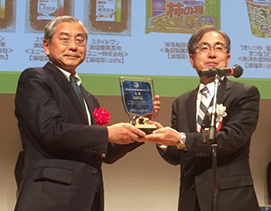 授賞式で盾を贈られる佐藤勇社長(左)