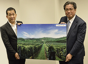 余市町のブドウ畑をイメージしたパネルを持つ平野伸一社長(右)と嶋保余市町長
