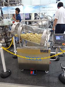 手動バッチ計量式シーズニングシステム「MaBS」。展示会では中が見えやすいようスケルトン仕様で展示した