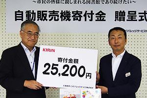 鈴木浩一小樽市図書館長(左)と北海道キリンビバレッジサービス高島正樹支店長