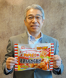 「若鶏ももからあげ チキチキボーン味」を手にする鶴田道太社長