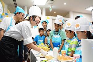 子どもたちに手本を見せるモンテールの山口実咲さん(手前左)