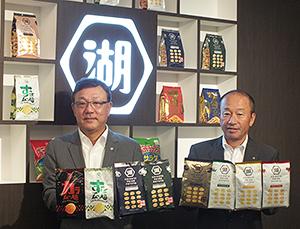 湖池屋の成長を担うプレミアム商品を手にする佐藤章社長(左)と小池孝会長