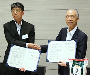 握手する雑賀慶二東洋ライス社長(右)と庭野吉也東都生協理事長