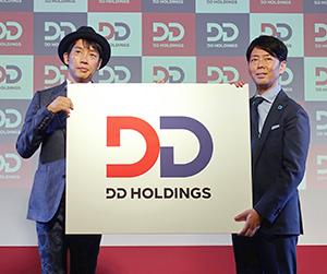 DDホールディングス企業ロゴを紹介する松村厚久社長(左)と佐藤可士和氏