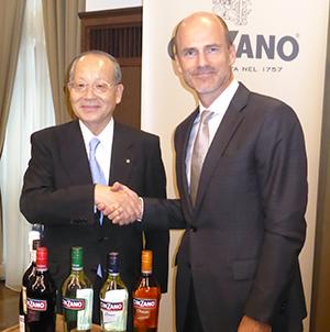 「チンザノ」展開商品を前に握手を交わす松沢幸一社長(左)とカンパリ社のジャスティン・ウエストン氏