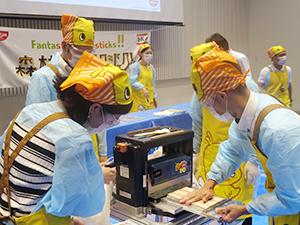 オリジナルマシンを使って箸づくりに取り組む東京本社社員