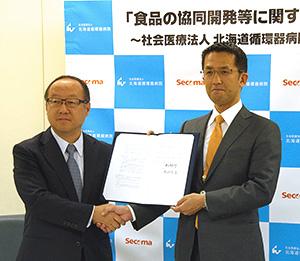 セコマの丸谷智保社長(左)と北海道循環器病院の津久井宏行理事長