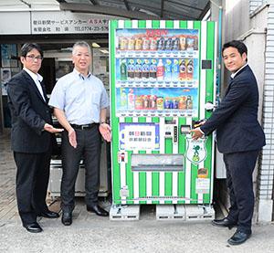 アミティエSC京都応援自動販売機。左から中西浩二課長、和田保則会長、清野暁部長
