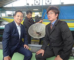 中野義久ヤマナカ社長(左)と齋場直樹ハイランドファーム東濃社長。後方のエビは出荷時(20g)の約半分のサイズ