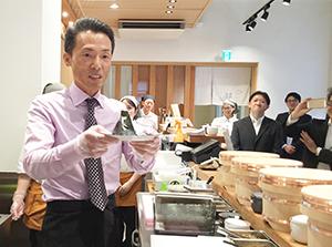 おにぎり専門店をオープンした神明。最初のにぎりを藤尾益雄社長が握る