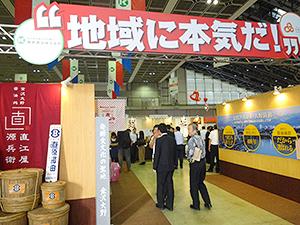 カナカン(石川県)はトモシアHDの新ビジョンのスローガン「地域に、本気だ!」を会場入り口に掲げ、地域商材に注力