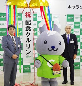 左から藤岡義幸配食事業部長、「クルリン」、中島則裕専務理事
