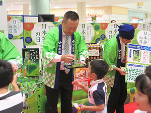 お茶の試飲を勧める本庄大介社長(左)