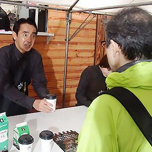 ホットミルクを手渡しするローソンの竹増貞信社長