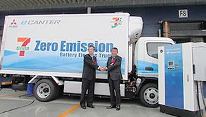 配送用EVの前で握手する古屋一樹社長(右)と松永和夫三菱ふそうトラック・バス会長