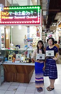 ヤンゴンにある「シンピューレーお土産店」。スタッフと写る新谷夢さん(右) =ミャンマー・ヤンゴンで。提供写真