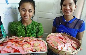 ヤンゴンにある「シンピューレーお土産店」のミャンマー人スタッフたち。頬にはミャンマー女性の化粧である「タナカ」が見える =ミャンマー・ヤンゴンで。提供写真