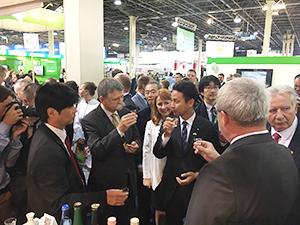 日本パビリオンでハンガリー政府要人に日本酒を紹介する谷合正明農林水産副大臣(中央(右))