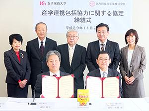 女子栄養大学・香川明夫学長(写真前列左)とあみ印食品工業・前原照雄社長(同右)